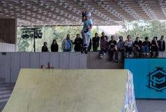 Adolescente en el casco que hace trucos en pcteres de ruedas en una rampa Imagen de archivo