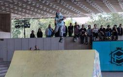 Adolescente en el casco que hace trucos en pcteres de ruedas en una rampa Imagenes de archivo