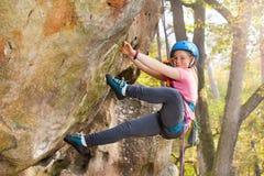 Adolescente en el casco que sube en la ruta de la roca Foto de archivo