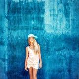 adolescente en el casquillo con una pared azul Foto de archivo