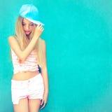adolescente en el casquillo con una pared azul Fotografía de archivo