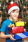Adolescente en el casquillo de la Navidad que sostiene los regalos Imágenes de archivo libres de regalías