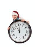 Adolescente en el casquillo de Papá Noel y del reloj grande Fotos de archivo