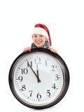 Adolescente en el casquillo de Papá Noel y del reloj grande Fotos de archivo libres de regalías