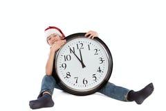 Adolescente en el casquillo de Papá Noel y del reloj grande Imágenes de archivo libres de regalías