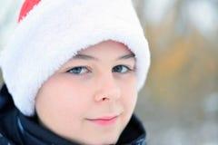 Adolescente en el casquillo Santa Claus al aire libre Foto de archivo