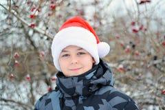Adolescente en el casquillo Santa Claus al aire libre Imagen de archivo