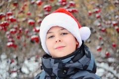 Adolescente en el casquillo Santa Claus en el fondo del Viburnum Foto de archivo libre de regalías