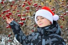 Adolescente en el casquillo Santa Claus en el fondo del Viburnum Fotos de archivo