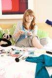 Adolescente en el dormitorio desordenado que encera las piernas Foto de archivo
