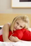 Adolescente en el dormitorio que abraza la almohadilla Imagen de archivo