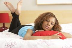 Adolescente en el dormitorio que abraza la almohadilla Foto de archivo libre de regalías