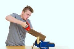 Adolescente en el entrenamiento profesional usando la sierra de la mano imagen de archivo