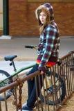 Adolescente en el estante de la bici Fotos de archivo