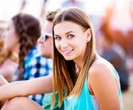 Adolescente en el festival de música del verano, sentándose en la tierra Foto de archivo