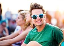Adolescente en el festival de música del verano, sentándose en la tierra Imagenes de archivo