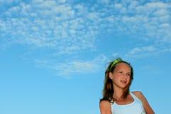 Adolescente en el fondo del cielo azul Foto de archivo