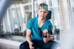 Adolescente en el gimnasio que trabaja con pesas de gimnasia Fotografía de archivo libre de regalías