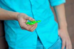 Adolescente en el hilandero de la persona agitada de la tenencia de la mano Foto de archivo libre de regalías