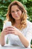 Adolescente en el jardín que envía el mensaje de texto Fotografía de archivo libre de regalías
