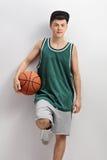 Adolescente en el jersey verde que lleva a cabo baloncesto y que se inclina en la pared Fotografía de archivo libre de regalías