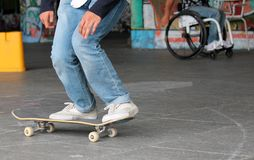 Adolescente en el monopatín con el hombre discapacitado en silla de ruedas detrás Foto de archivo