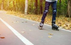 Adolescente en el movimiento rollerblading en parque del otoño Foto de archivo