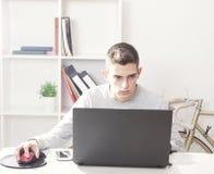 Adolescente en el ordenador portátil casero Imagenes de archivo