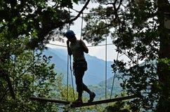 Adolescente en el parkour de la cuerda contra las montañas Fotografía de archivo libre de regalías