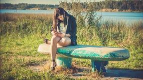 adolescente en el parque con su teléfono Imágenes de archivo libres de regalías