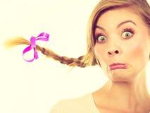 Adolescente en el pelo de la trenza que hace la cara divertida Fotografía de archivo