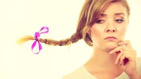 Adolescente en el pelo de la trenza que hace la cara de pensamiento Imágenes de archivo libres de regalías