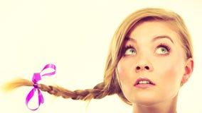 Adolescente en el pelo de la trenza que hace la cara de pensamiento Foto de archivo