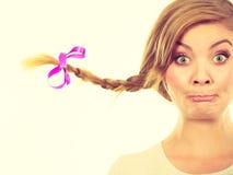 Adolescente en el pelo de la trenza que hace la cara divertida Fotos de archivo