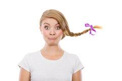 Adolescente en el pelo de la trenza que hace la cara divertida Imagenes de archivo