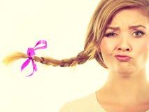 Adolescente en el pelo de la trenza que hace la cara divertida Foto de archivo libre de regalías