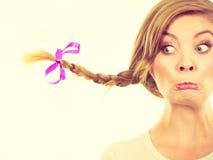 Adolescente en el pelo de la trenza que hace la cara divertida Foto de archivo