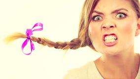 Adolescente en el pelo de la trenza que hace la cara enojada Fotografía de archivo
