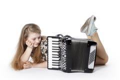Adolescente en el piso del estudio con el acordeón Imágenes de archivo libres de regalías