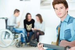Adolescente en el sitio que toca la guitarra Fotos de archivo libres de regalías
