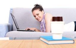 Adolescente en el sofá usando la computadora portátil Foto de archivo libre de regalías
