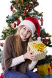 Adolescente en el sombrero de Papá Noel con el presente debajo del árbol de navidad Fotos de archivo