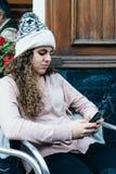 Adolescente en el sombrero de punto que manda un SMS con el teléfono celular Fotos de archivo libres de regalías