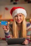 Adolescente en el sombrero de santa con la PC de la tableta que muestra la tarjeta de crédito Imagenes de archivo