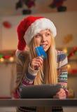 Adolescente en el sombrero de santa con la tarjeta de crédito y la PC de la tableta Imagen de archivo