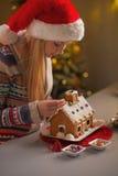 Adolescente en el sombrero de santa que adorna la casa de la galleta de la Navidad Foto de archivo libre de regalías