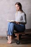 Adolescente en el suéter que lee un libro Fondo gris Imagen de archivo libre de regalías