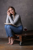 Adolescente en el suéter que presenta con el libro y el vidrio de vino Fondo gris Foto de archivo libre de regalías