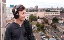 Adolescente en el tejado de la casa en los auriculares Imágenes de archivo libres de regalías