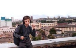Adolescente en el tejado de la casa en los auriculares Imagen de archivo libre de regalías